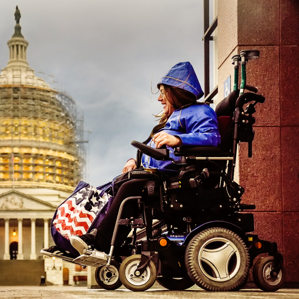Woman in a motorized wheelchair with U.S. Capital in the background