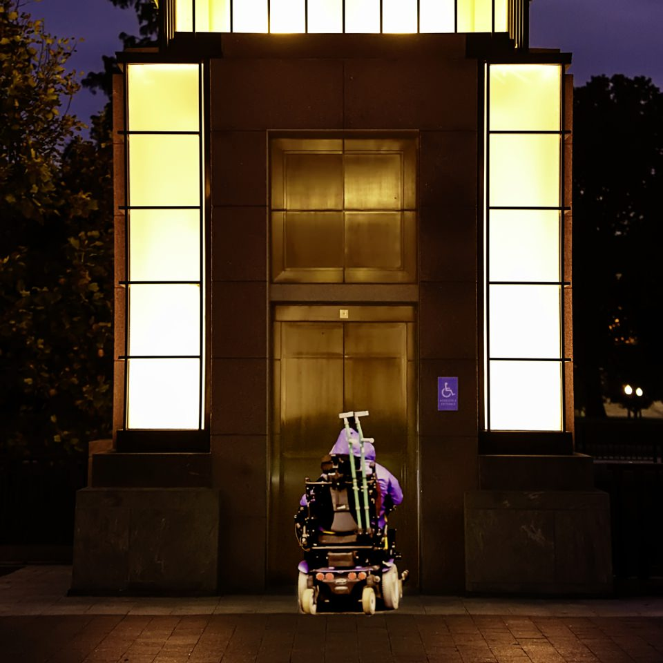 Woman in a motorized wheelchair waiting for an elevator in Washington, D.C.
