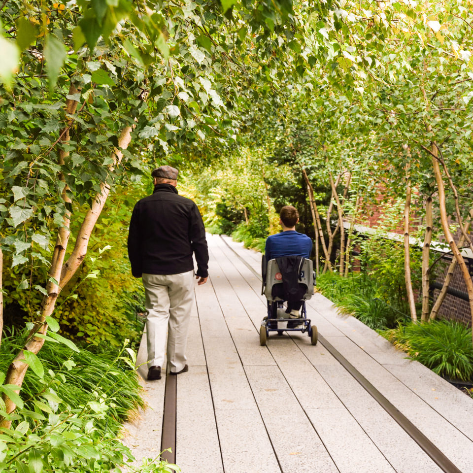 Man in a wheelchair and a companion walk on a nature path.